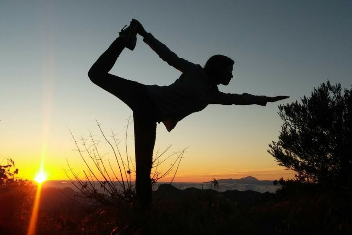 Woman doing yoga on a mountain top